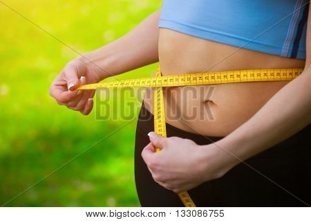 Sport girl measuring waist. Sports. Reducing excess weight. Healthy lifestyle.