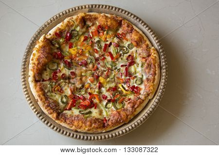A Large Pizza topped with Bell Peppers and Jalapeños