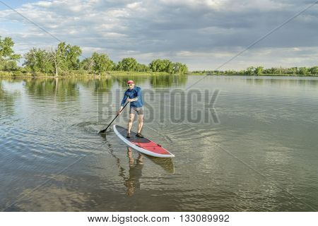 senior male paddler on a paddleboard, lake in northern Colorado with an early summer scenery