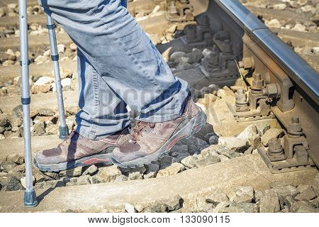 Disabled man with crutches on railway .