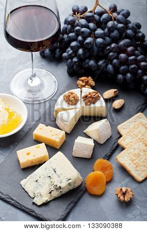 Assortment of cheese with honey nuts and grape on a modern cutting board slate background