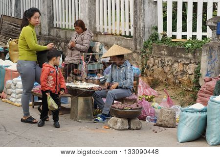 LUANG PRABANG, LAOS - FEBRUARY 13, 2016: People on the morning open air market of Luang Prabang on February 13, 2016 in Laos, Asia