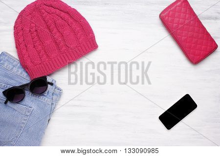 Women's everyday objects and winter outfit on white wooden background. Copyspace.