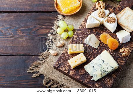 Assortment of cheese with honey nuts and grape on a rustic cutting board wooden background
