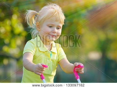 Portrait of a cute little baby girl walking with pram outdoors, happy child with toys playing in the park on a bright sunny day, preschoolers daycare