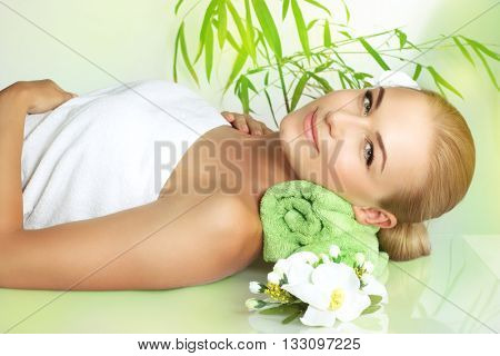 Beautiful calm woman lying down on the massage table and enjoying spa procedure, alternative medicine, healthy lifestyle