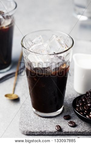 Ice coffee in a tall glass and coffee beans on a grey stone background