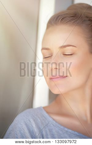 Closeup portrait of a nice female with closed eyes standing near the window at home and enjoying warm sun light