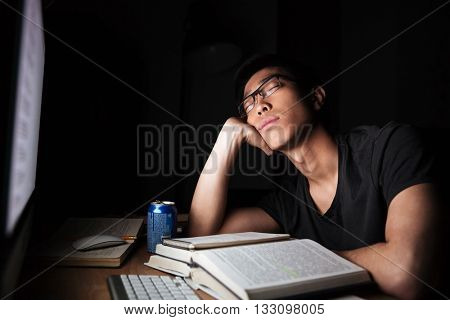 Tired exhausted asian young man studying and sleeping in front of computer in nighttime