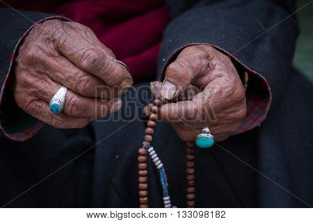 Old Tibetan woman holding buddhist rosary in Hemis monastery Ladakh India. Hand and rosary close up