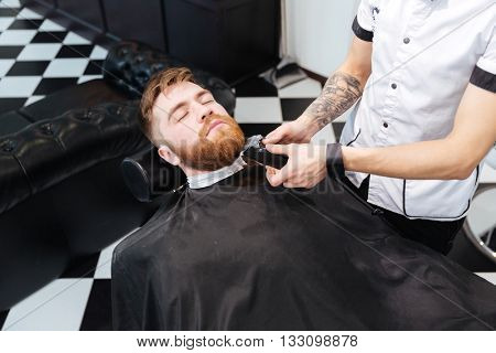 Barber shaving beard of his client with hair clipper