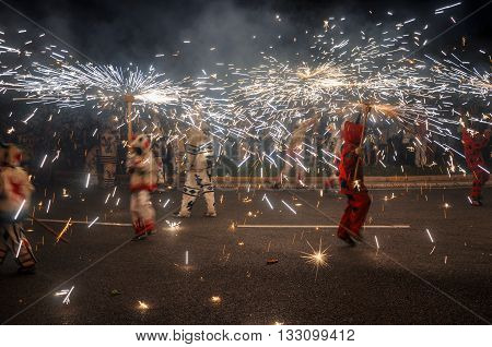 Traditional correfocs (fire runs) performance (Spanish: Baile de Diablos Catalan: Ball de Diables or Correfocs). Group of individuals dressed as devils and dancing with lighting fireworks fixed on devil's pitchforks. Reus Spain.