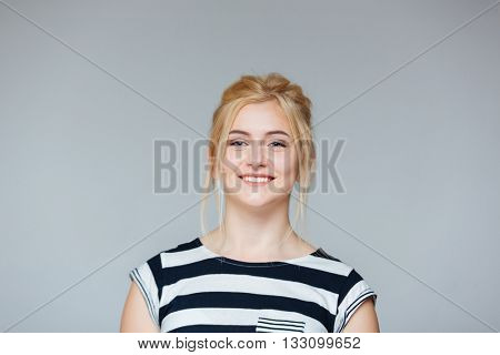 Portrait of cheeful pretty young woman in striped t-shirt over white background