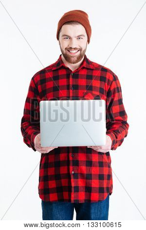 Close-up portrait of a handsome bearded smiling man holding laptop isolated on the white background