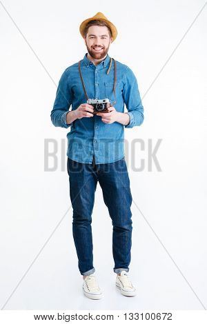 Handsome young hipster guy holding retro camera wearing hat isolated on the white background