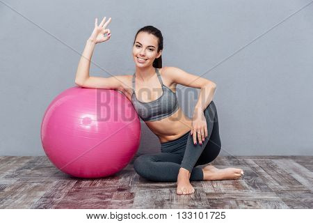 Young beautiful fitness girl with pink ball showing okay sign isolated on grey background