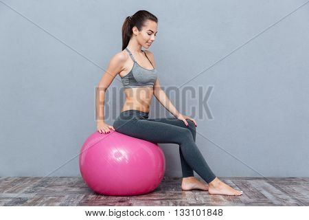 Fitness smiling girl sitting on pink fitness ball isolated on grey background