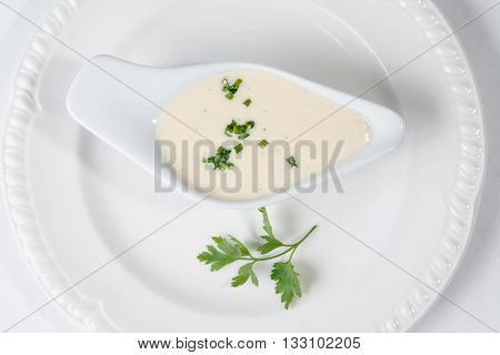 Tasty Bechamel sauce or white sauce with fresh greenery.