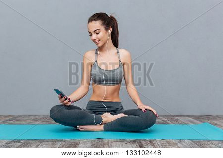 Young woman listening to music with earphones in exercise outfit isolated on grey background