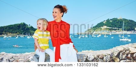 Happy Mother And Child In Front Of Lagoon Looking In Distance