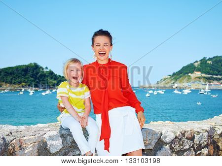 Smiling Mother And Daughter In Front Of Lagoon With Yachts