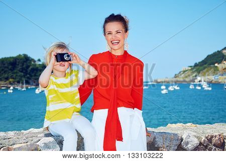 Happy Mother And Child Taking Photo In Front Of Lagoon