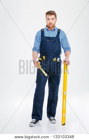 Full length portrait of a bearded male builder holding waterpass and measure tape isolated on a white background