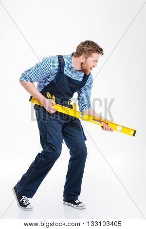 Full length portrait of a funny male builder posing with waterpas isolated on a white background