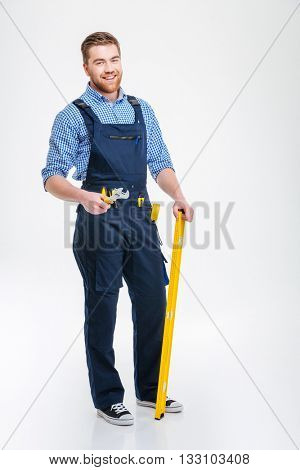 Full length portrait of a happy male builder standing with equipment isolated on a white background