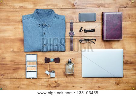 Travel concept shirt, mobile phone, earphones, laptop, perfume, eyeglasses, watch, lighter, book, cigarettes on the desk