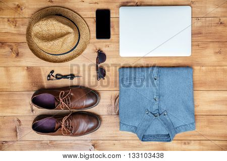 Travel concept shoes, shirt, mobile phone, earphones, laptop, hat, eyeglasses on the desk