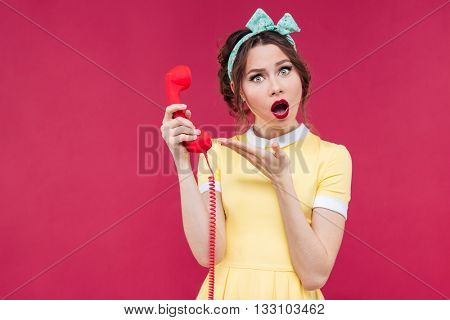 Wondered beautiful pinup girl in yellow dress holding red receiverand talking on telephone over pink background