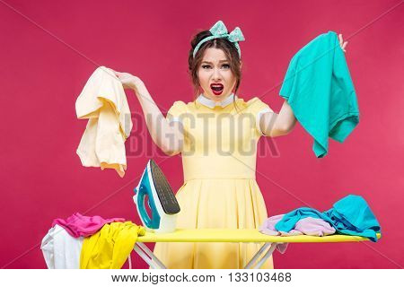 Disappointed angry young woman holding clothes and shouting near ironing board over pink background