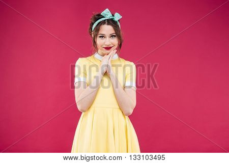 Happy beautiful pinup girl in yellow dress and headband over pink background