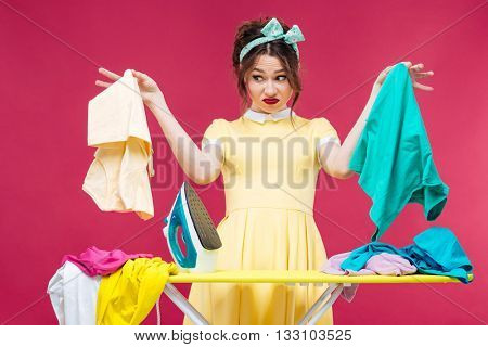 Unhappy irritated young woman holding and ironing clothes over pink background
