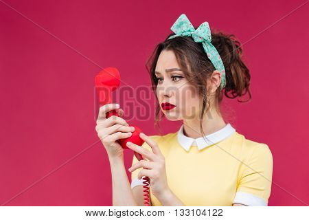 Portrait of sad pretty young woman using red receiver and talking on telephone over pink background