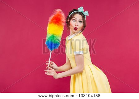 Charming playful pinup girl with colorful cleaning broom over pink background