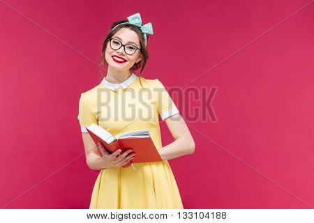 Happy lovely pinup girl in glasses reading a book over pink background