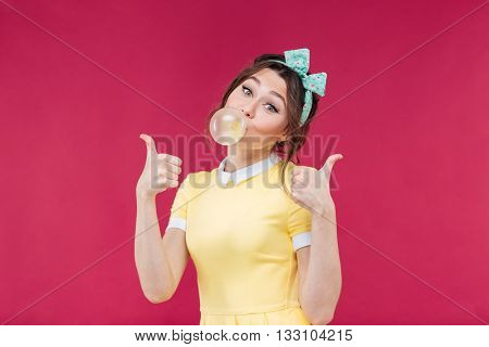Happy lovely young woman in yellow dress with pink bubble of chewing gum over pink background