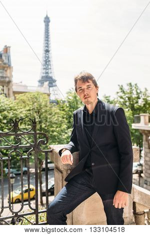 Man in black the Eiffel tower on the background. travel background
