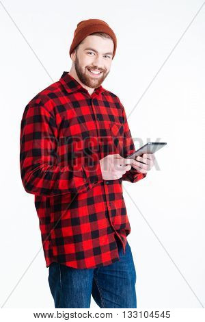 Smilling young hipster guy using pc tablet isolated on the white background