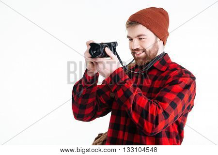 Hipster young man takes a picture with a vintage photo camera isolated on the white background