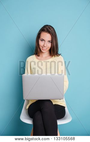 Smilling young woman using laptop pc computer isolated on the blue background