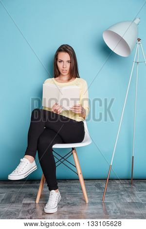 Pretty young atractive woman looking at camera and holding book isolated on the blue background