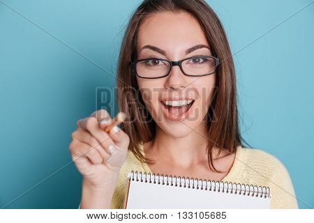 Close-up of a cute young girl pointing at camera holding notebook over blue background