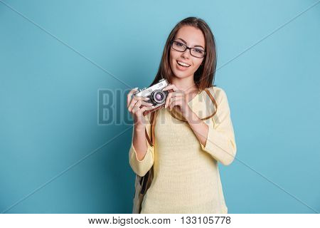 Young pretty girl taking photo using photocamera isolated on the blue background