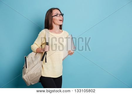 Beautiful smiling girl with bagpack and notebook isolated on the blue background