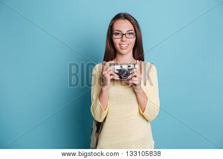 Young pretty girl taking photo using camera isolated on the blue background