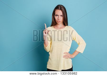 Serious pretty girl pointing finger up and looking at camera isolated on the blue background