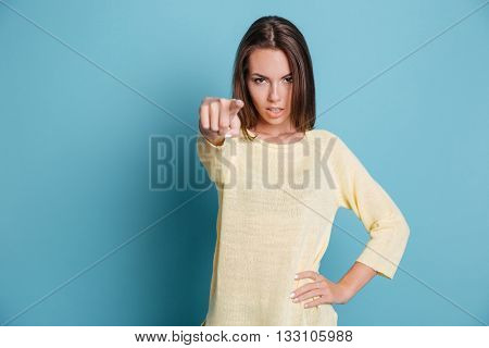 Beautiful confident girl pointing at camera isolated on the blue background